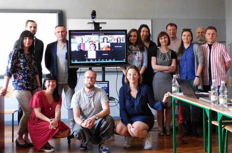 Grupa nauczycieli Liceum Banacha w Chorzowie w sali. Na ekranie telewizora uczestnicy spotkania w formie zdalnej.